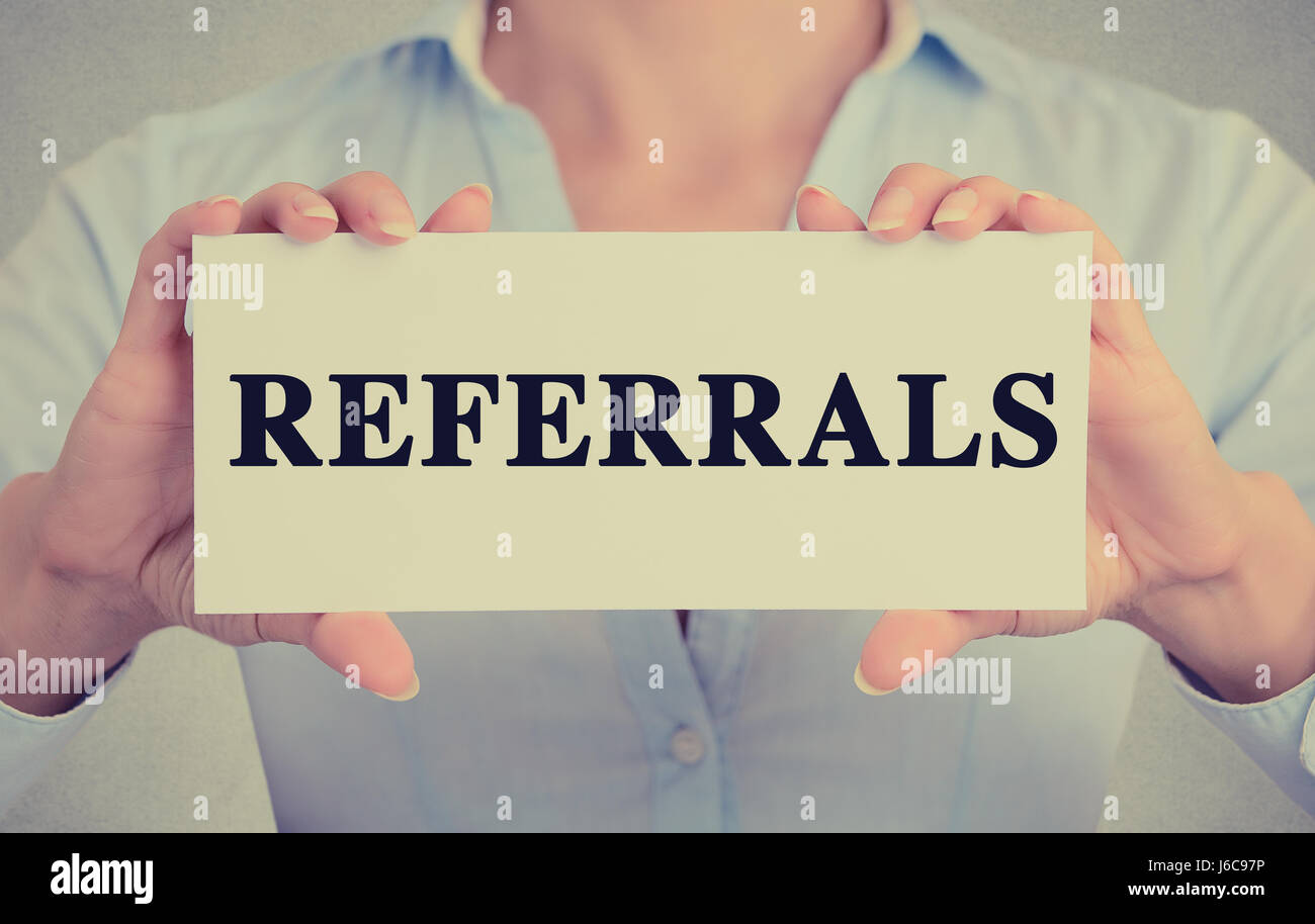 Businesswoman hands holding white card sign with referrals text message isolated on grey wall office background. - Stock Image