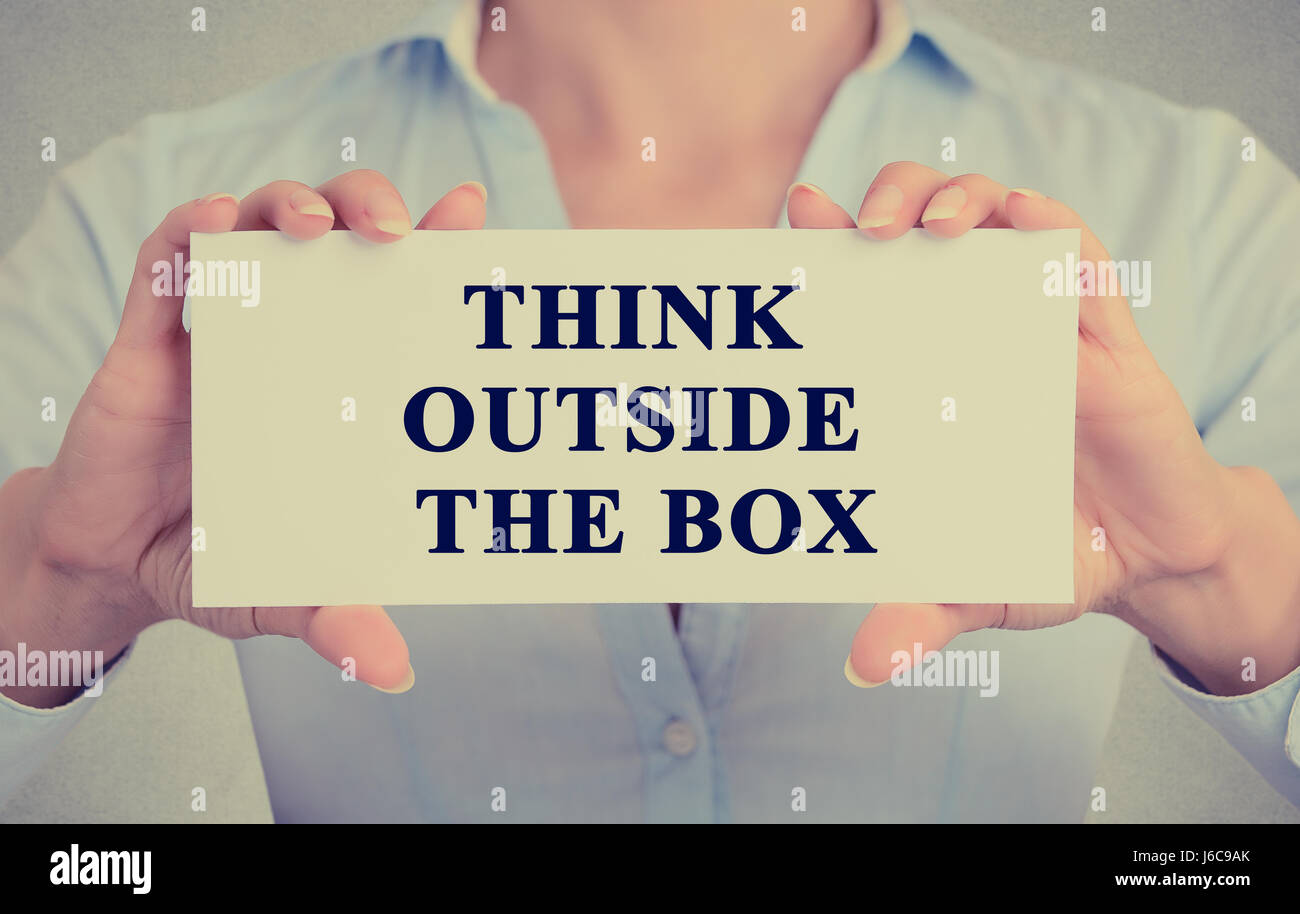 Closeup retro image businesswoman hands holding white sign or card with message think outside the box isolated on - Stock Image
