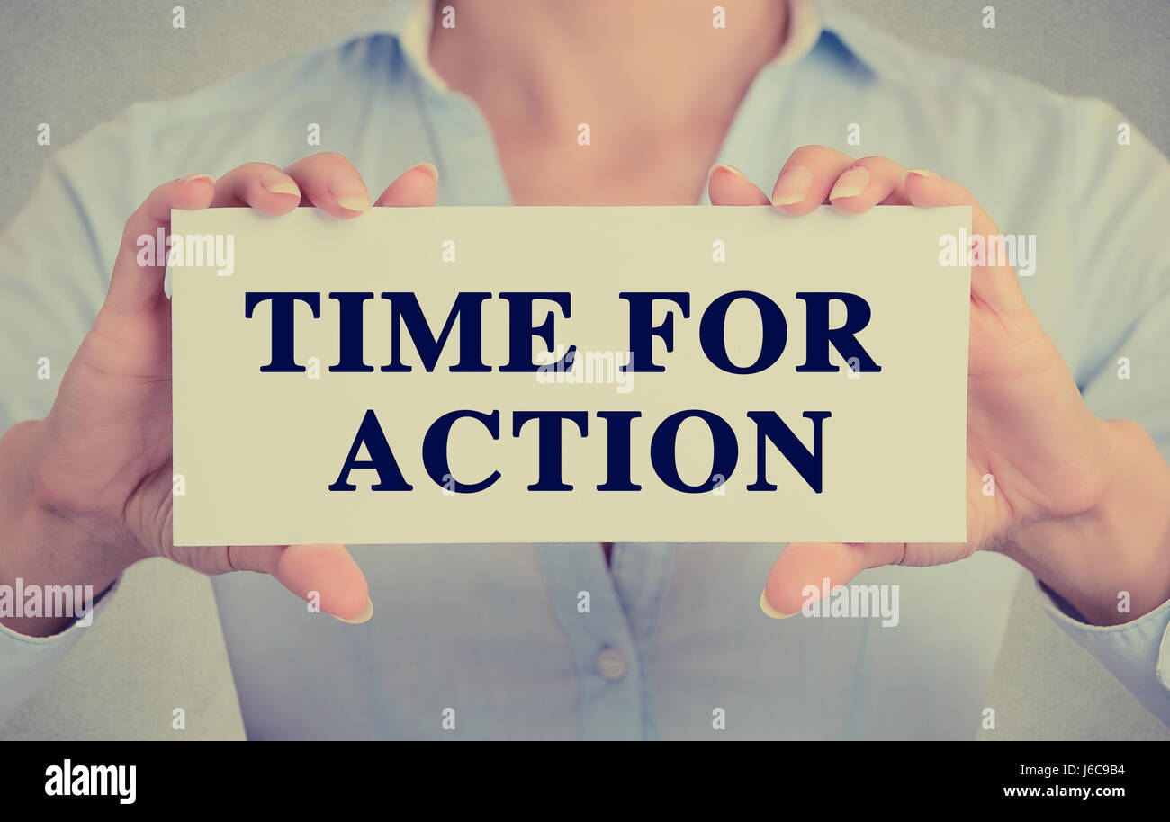 Closeup businesswoman hands holding white card sign with time for action text message isolated on grey wall office - Stock Image