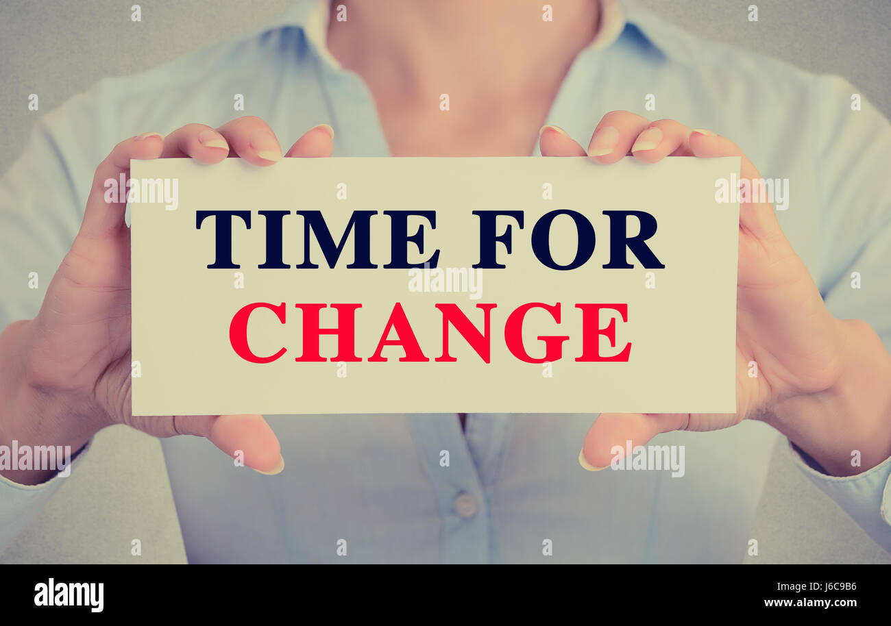 Businesswoman hands holding white card sign with time for change text message isolated on grey wall office background. - Stock Image