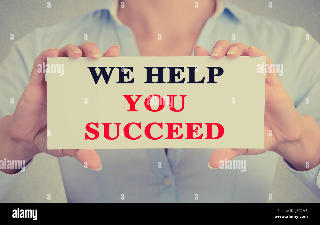 Businesswoman hands holding white card sign with we help you succeed text message isolated on grey wall office background. - Stock Image