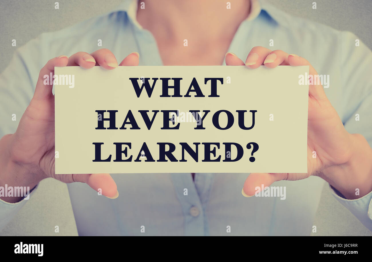 Closeup teacher hands holding white card sign with What have you Learned? question text message isolated on grey - Stock Image