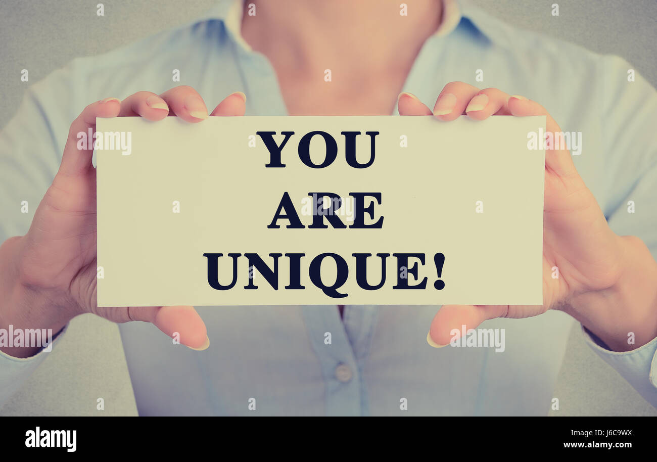 Closeup businesswoman hands holding white card sign with you are unique text message isolated on grey wall office Stock Photo