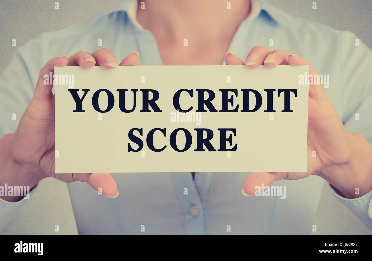 Closeup businesswoman hands holding white card sign with your credit score text message isolated on grey wall office - Stock Image