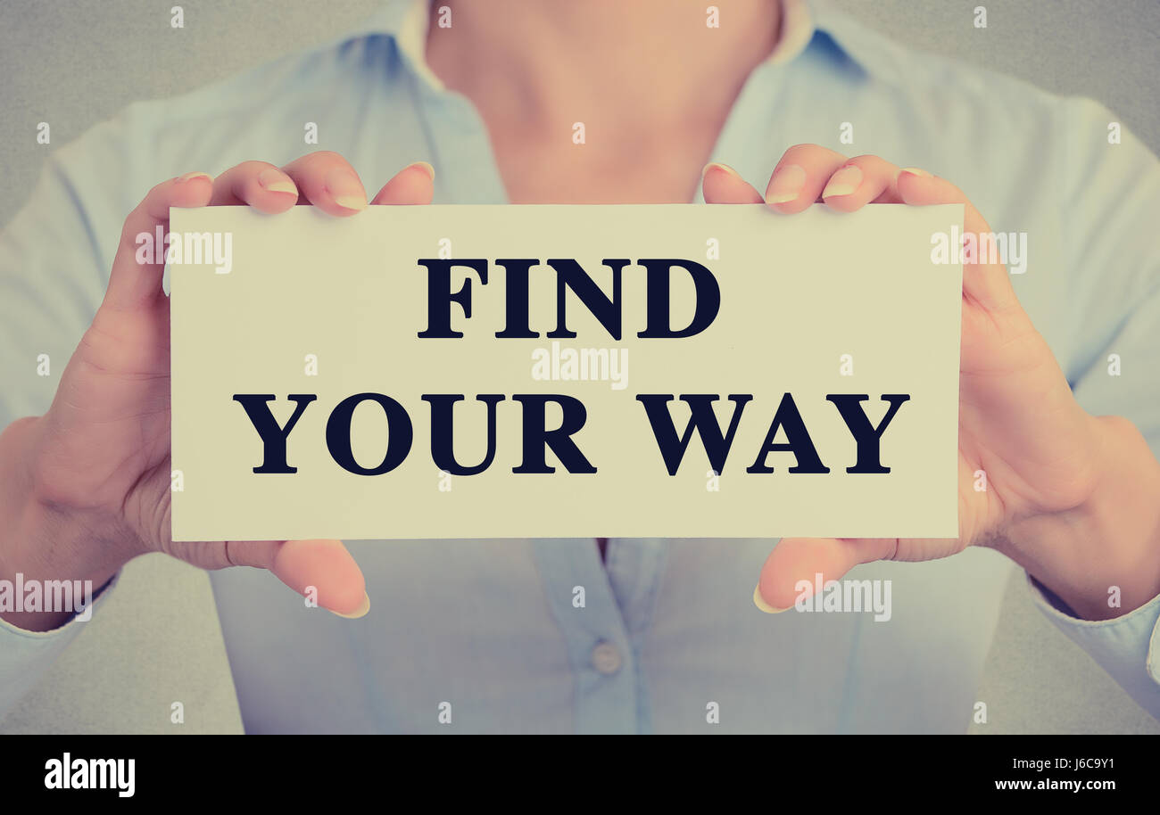 Closeup businesswoman hands holding white card sign with find your way text message isolated grey wall office background. - Stock Image