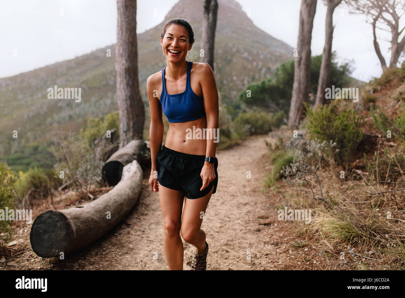 Shot of beautiful young asian woman standing on mountain trail and laughing. Healthy female runner in sportswear - Stock Image