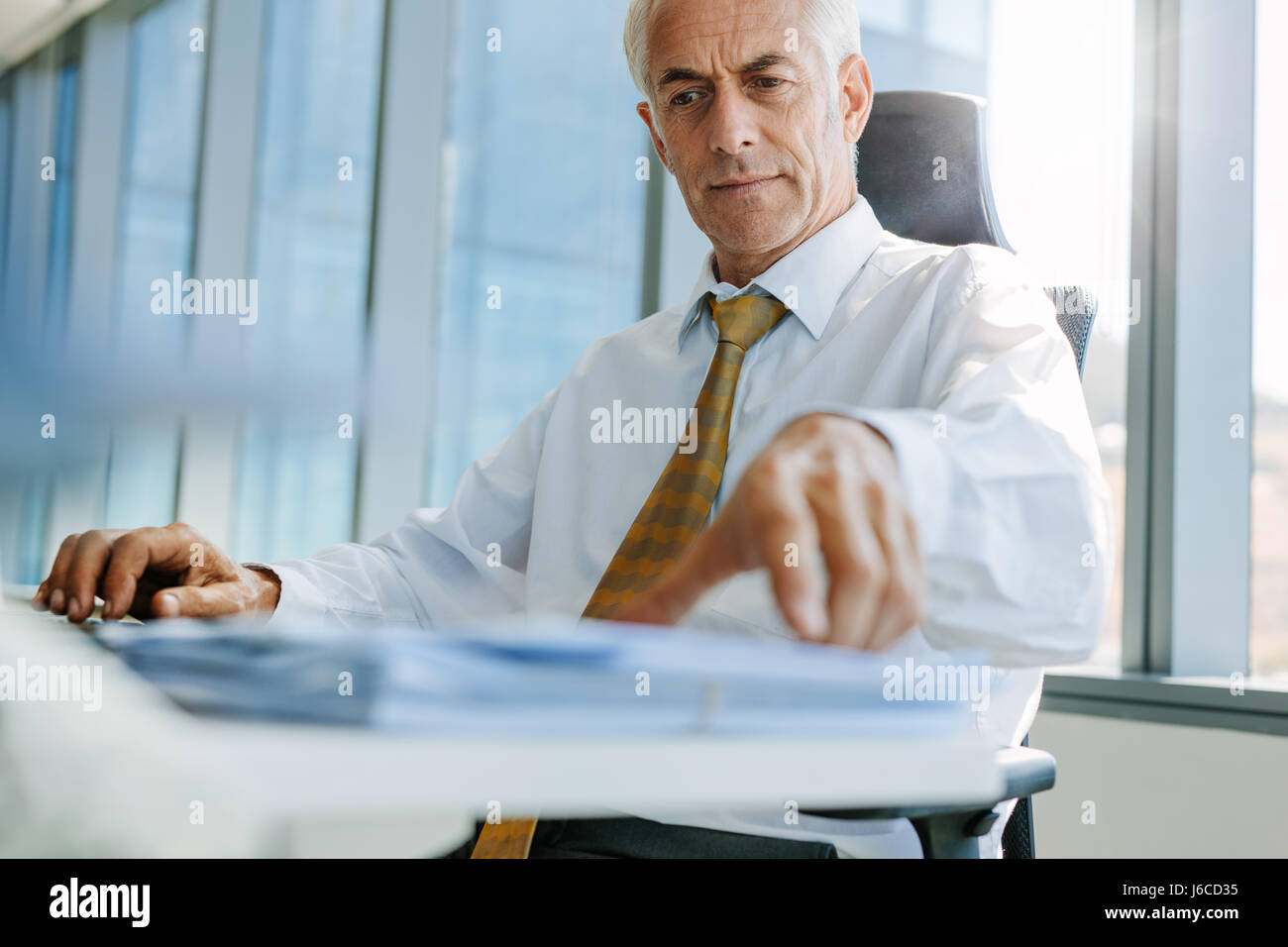 Shot of mature businessman sitting at his desk and working. Senior male entrepreneur in his office. - Stock Image