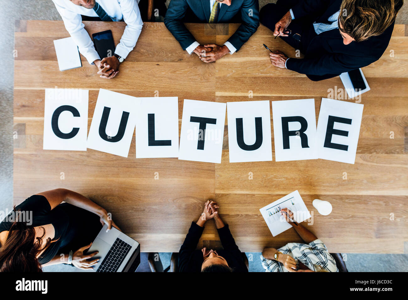 Group of business people with alphabets signs forming the word Culture on table. Top view of business people discussing - Stock Image