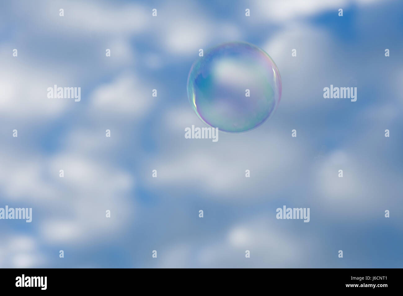 A bubble lifts into the blue and white sky. - Stock Image