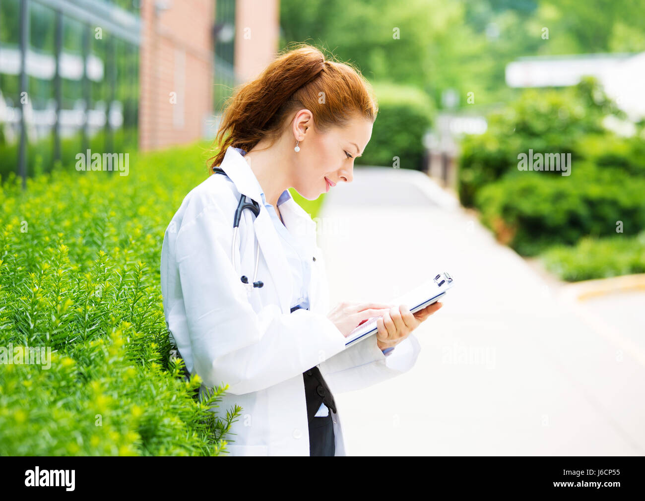 Portrait, young confident female doctor, healthcare professional reading patient chart isolated background outside - Stock Image