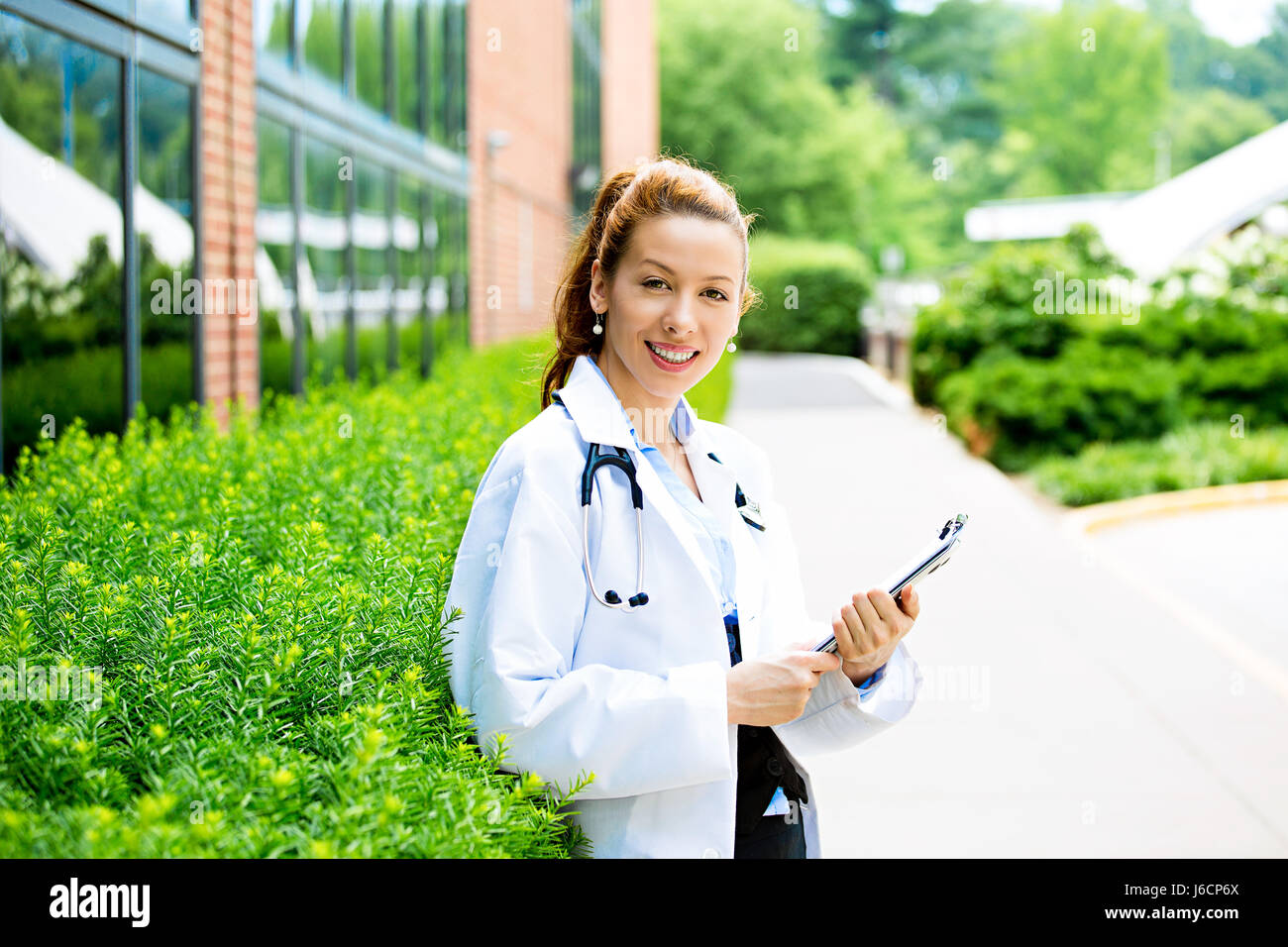 Closeup portrait young confident female doctor healthcare professional holding patient chart isolated background - Stock Image