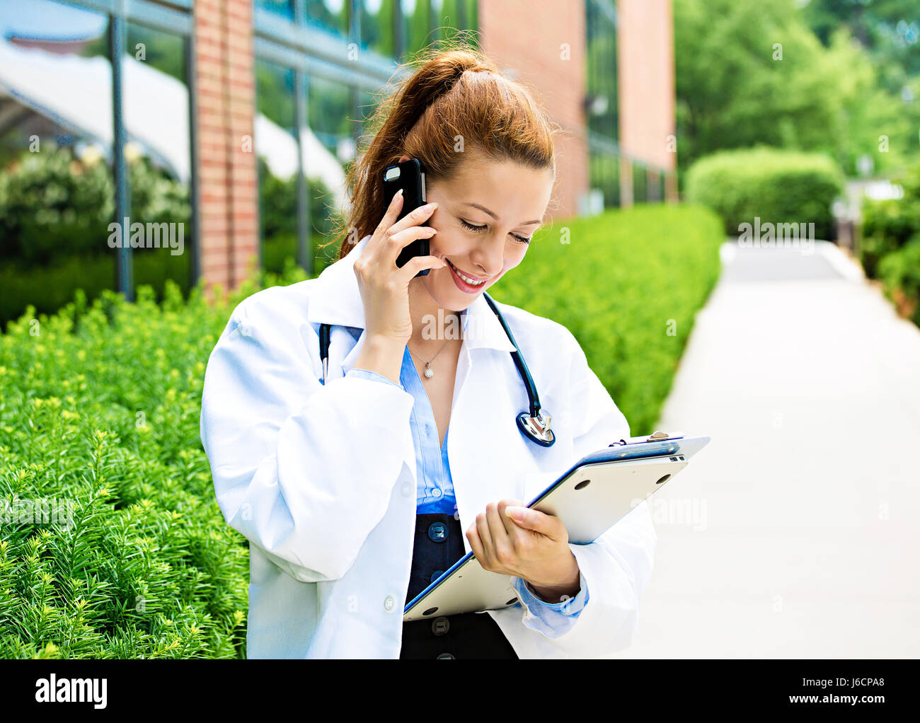 Closeup portrait, young smiling confident female doctor, healthcare professional talking on phone, giving consultation - Stock Image