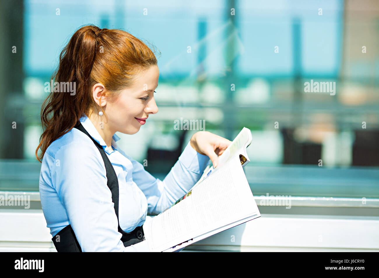 Closeup side view portrait business woman reading latest news in magazine, smiling happy, great stock market news - Stock Image