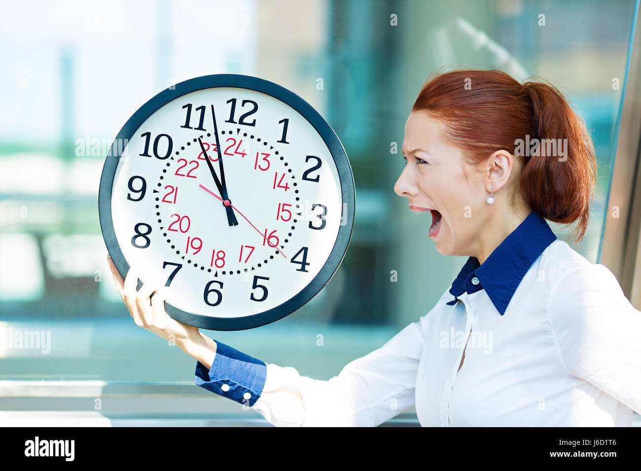 Closeup portrait business woman being late with clock in hands. Concept photo with young businesswoman in hurry - Stock Image