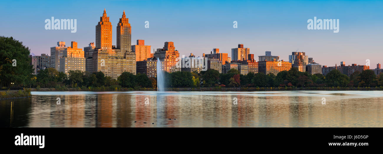 Panoramic view of Central Park West high-rise buildings and the Jacqueline Kennedy Onassis Reservoir at dawn. Upper - Stock Image