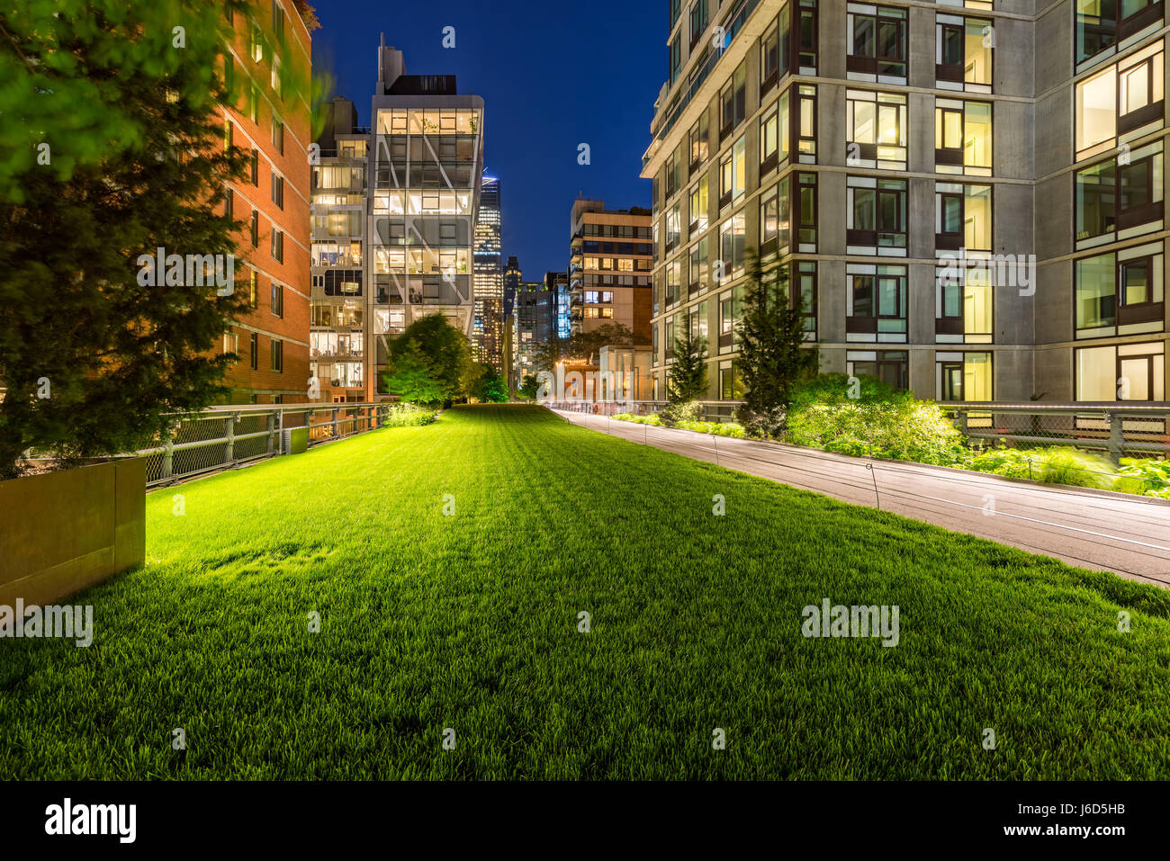 Highline promenade and lawn at twilight with city lights in the heart of Chelsea. Manhattan, New York City - Stock Image