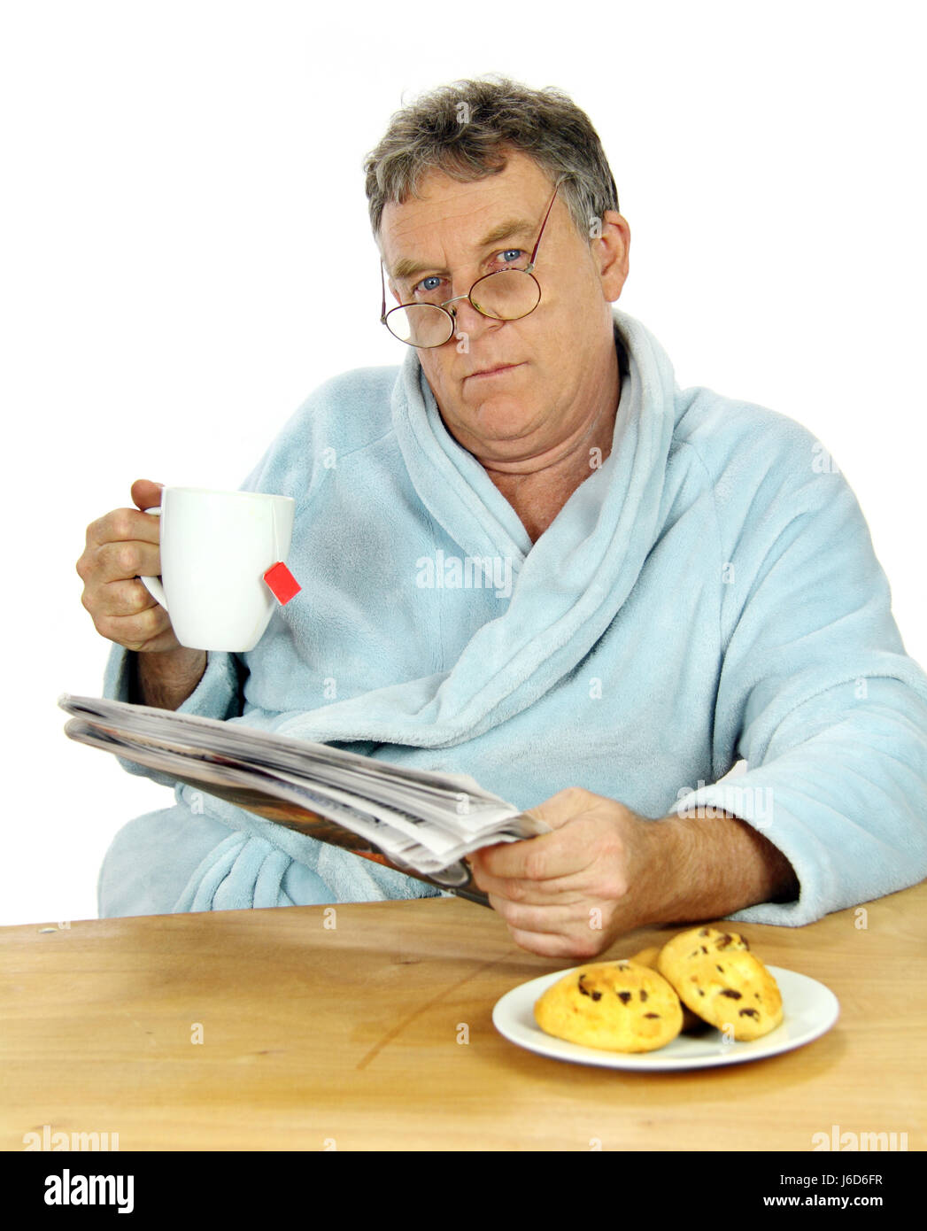 male masculine unhappy newspaper journal cup tea male masculine look glancing Stock Photo