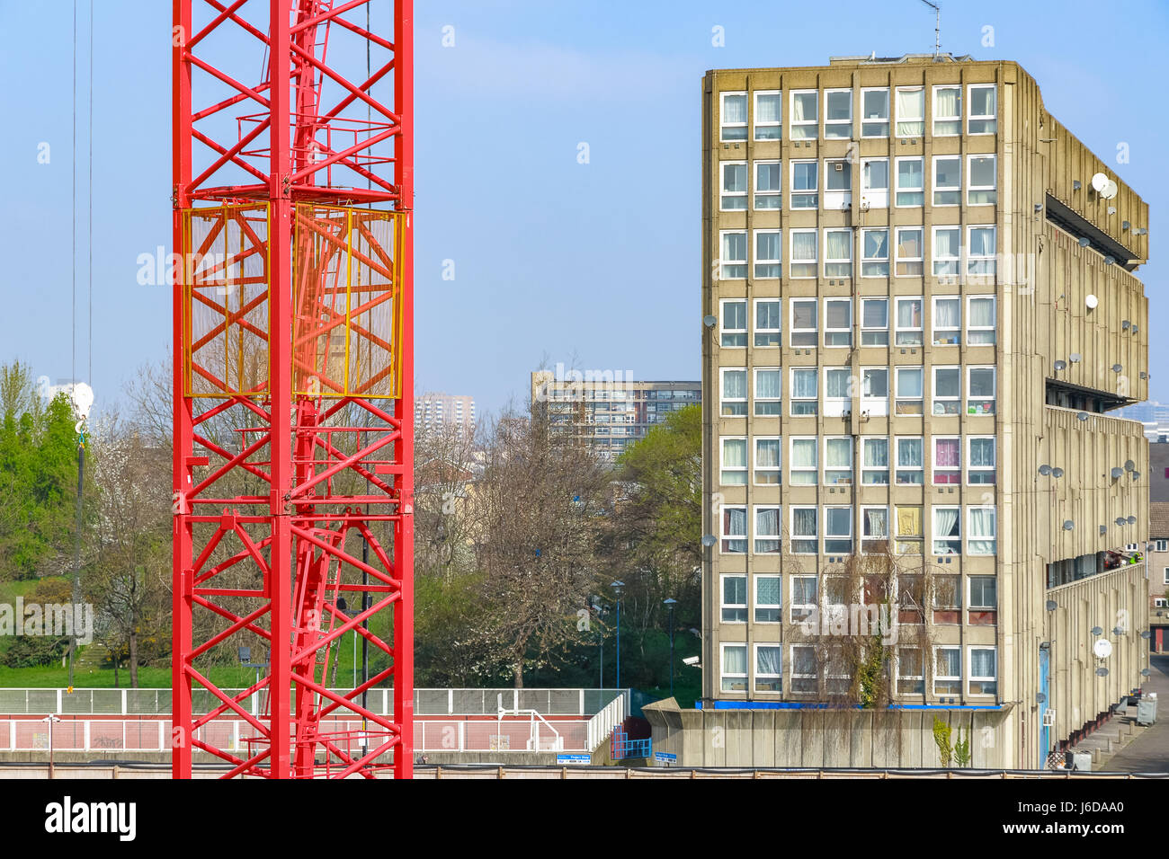 Red building cranes with East London council housing blocks in the background - Stock Image