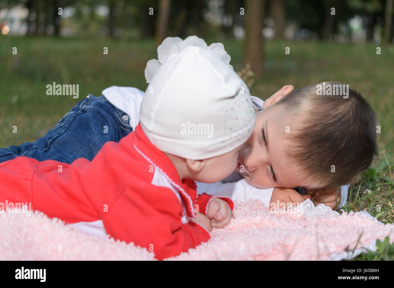 Underage boy with his little sister about something sweet deal. - Stock Image