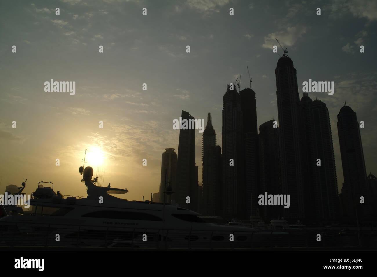 Sun rising over moored motor-cruiser towards silhouettes Dubai Marina Towers, Al Sufouh Road, Dubai International - Stock Image