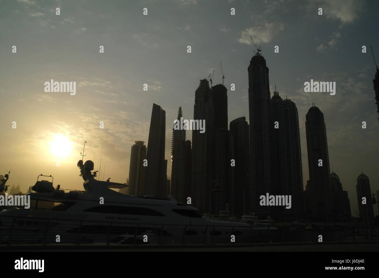 Sun rising to left of silhouettes Dubai Marina Towers from Al Sufouh Road, west end Dubai International Marina, - Stock Image