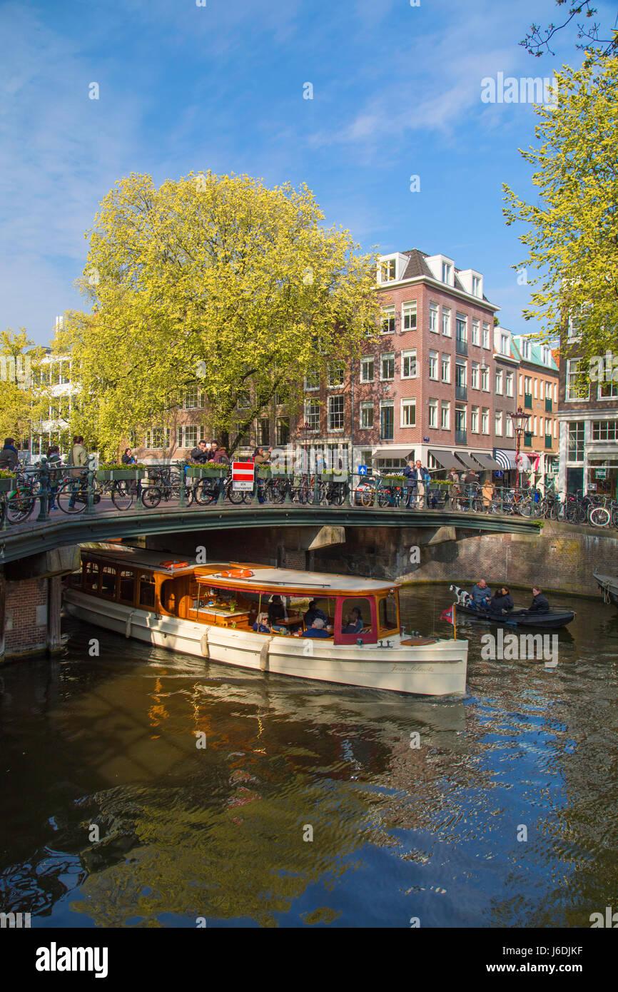 Boat passing under bridge of Prinsengracht canal, Amsterdam, Netherlands - Stock Image