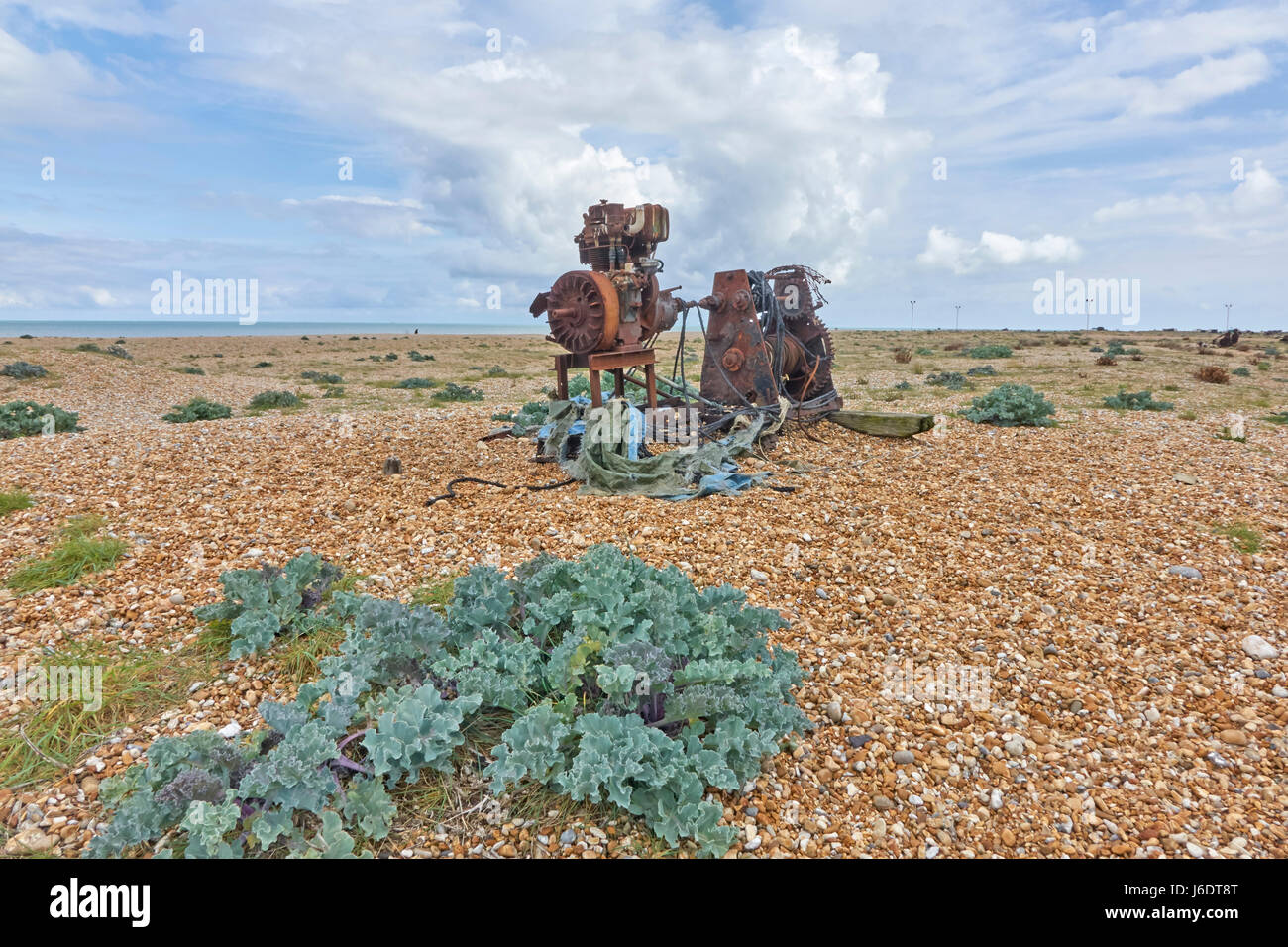 Dungeness Kent. Rusty old winch once used for hauling fishing boats up the steep shingle beach; now looking eerily - Stock Image