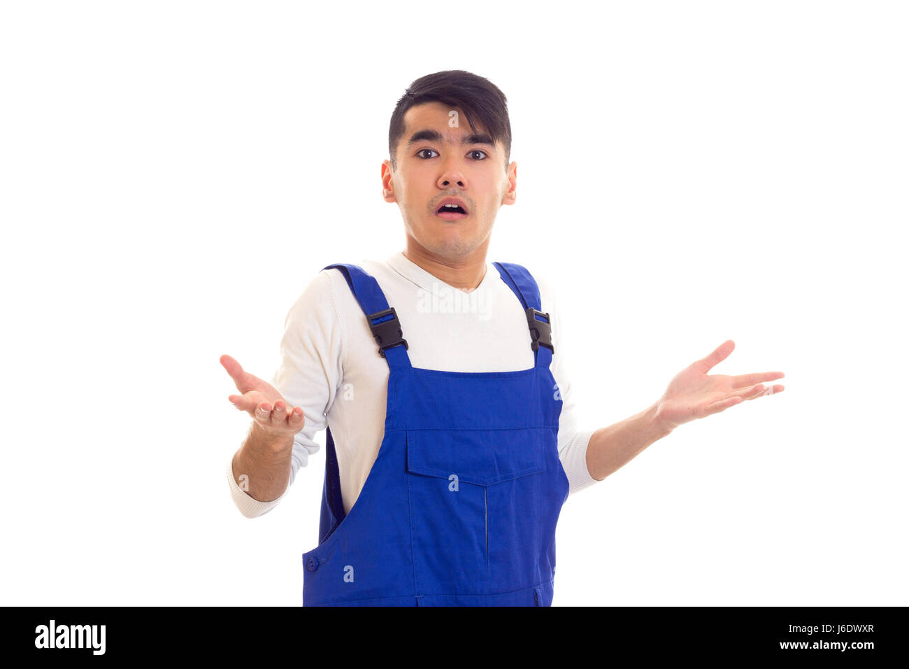 Young incomprehensible man in blue overall Stock Photo