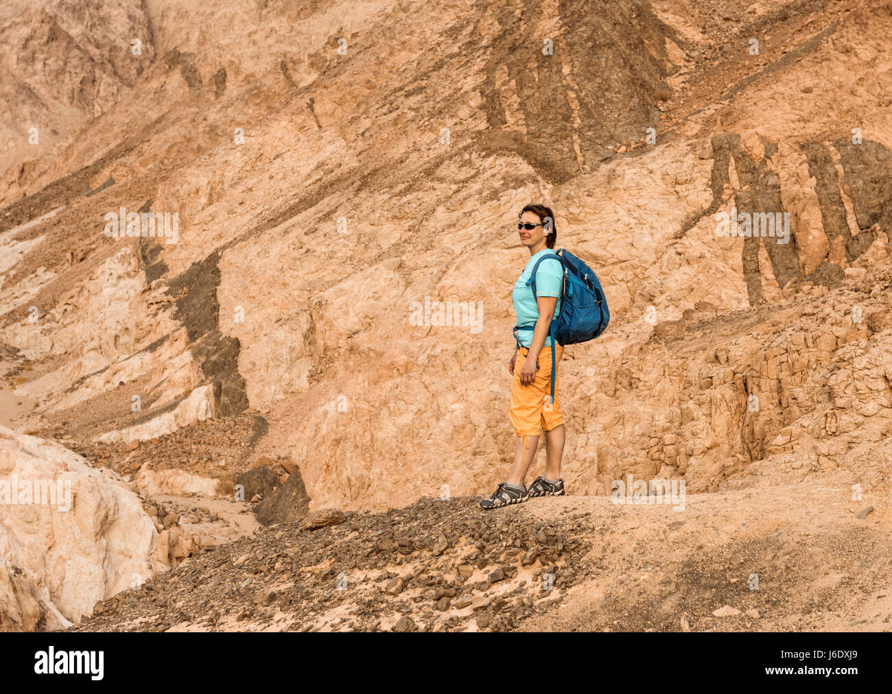 Woman Hiker with backpack enjoy view in desert - Stock Image