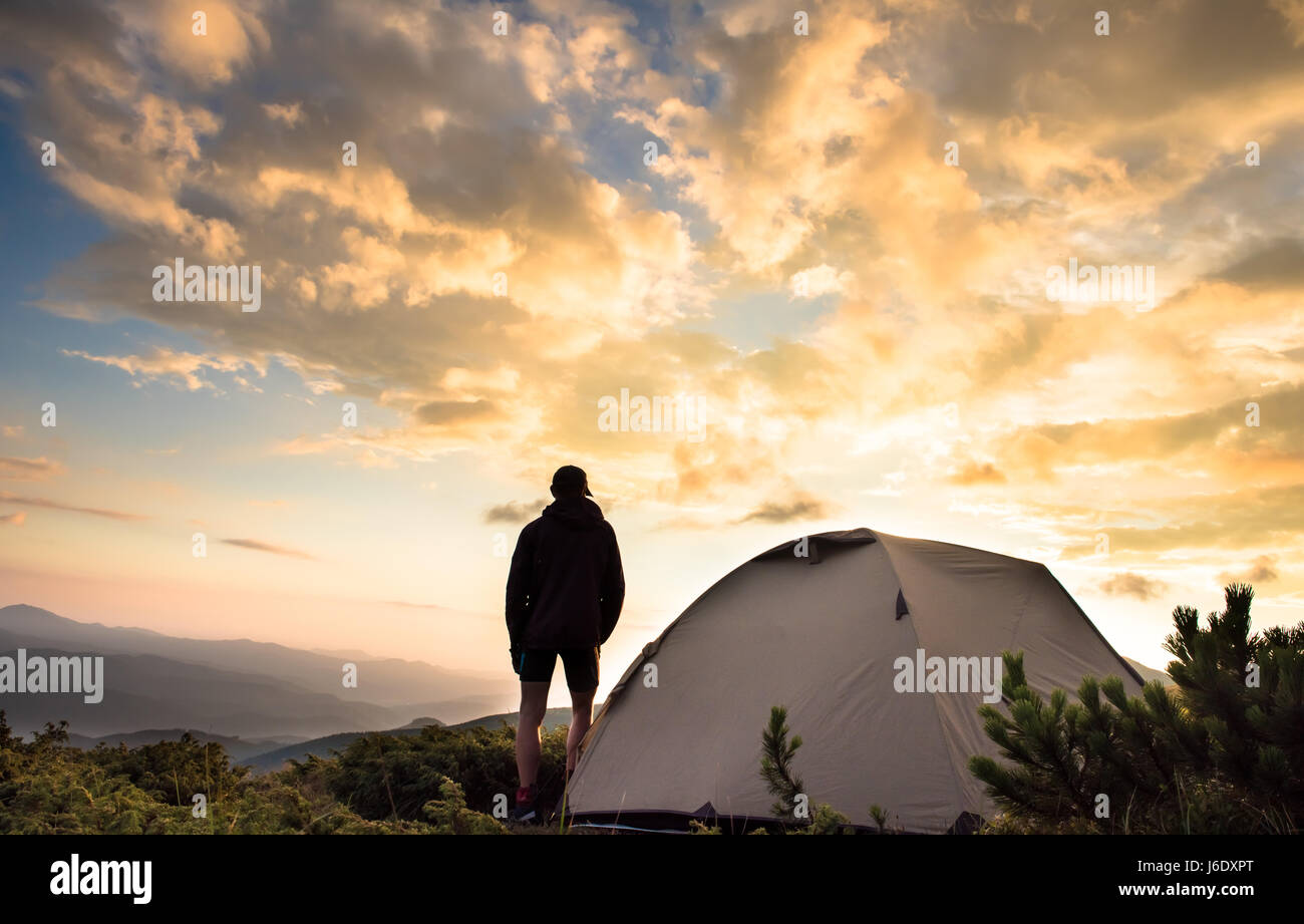 tourist tent and sportsman in mountains summertime - Stock Image