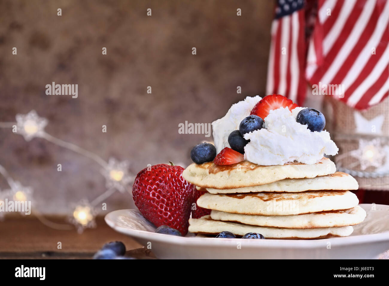 Pancakes served with blueberries, strawberries, and whipped cream against a rustic background. Perfect for fourth - Stock Image