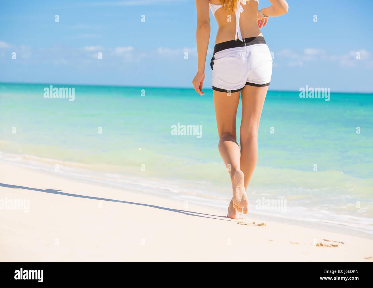 Beach travel. Woman walking on sand beach leaving ...