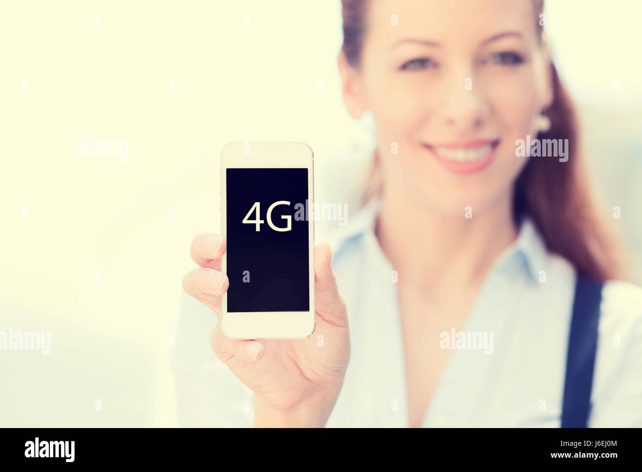 Smiling female holding mobile smart phone with 4G sign on screen isolated outside city background focus on smartphone. - Stock Image
