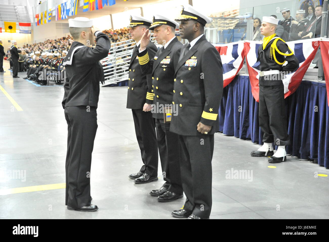 161216-N-CM124-295   GREAT LAKES, Ill. (Dec. 16, 2016) Chief of Naval Personnel Robert P. Burke salutes a recruit - Stock Image
