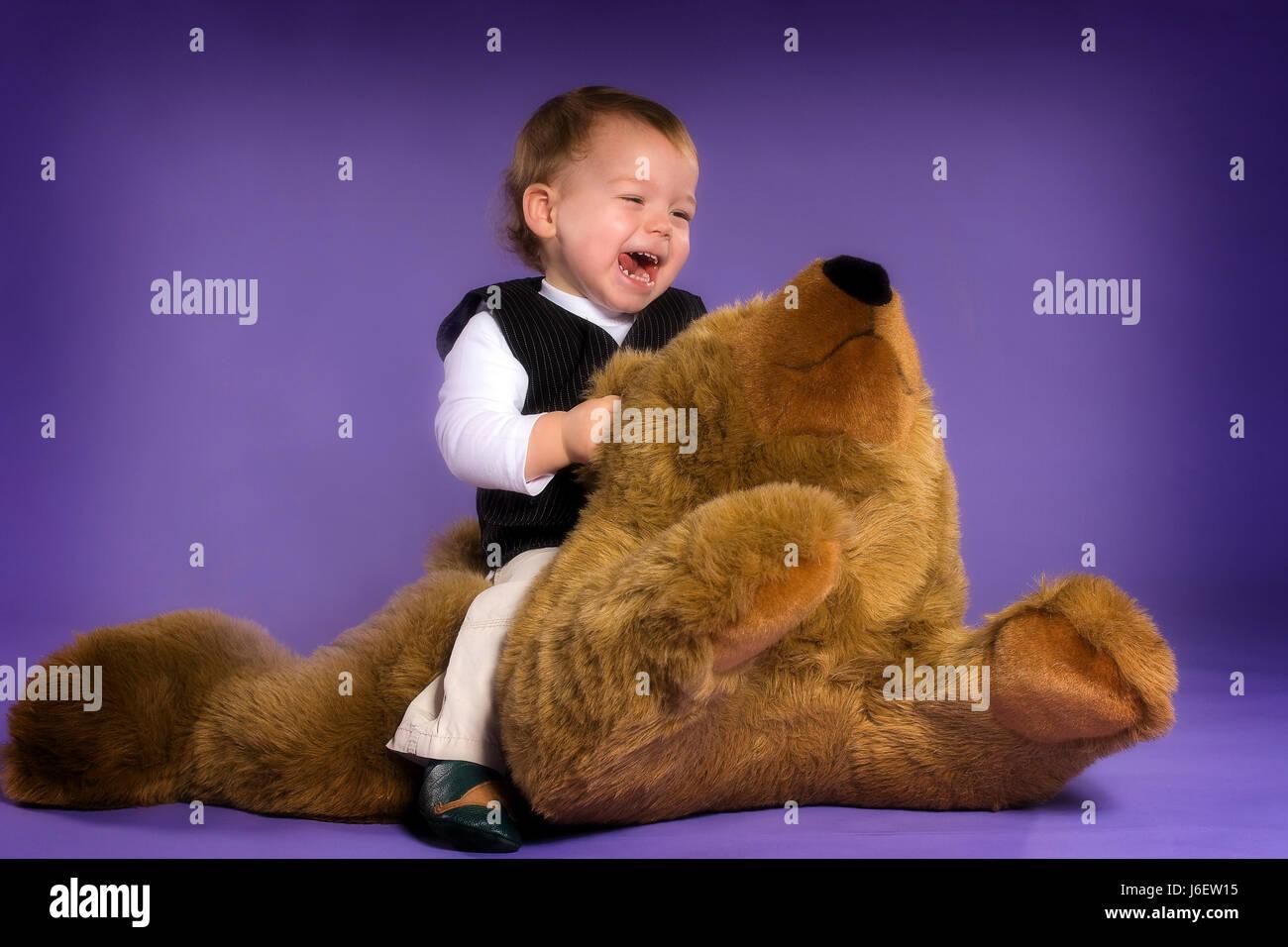 toddler riding on giant teddy Stock Photo