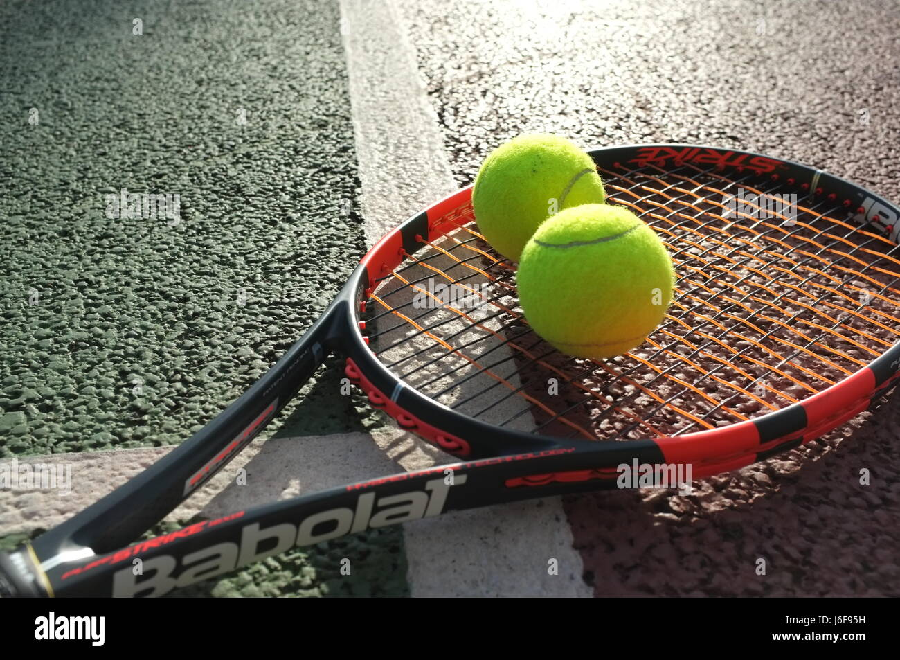 Tennis balls on a Babolat racquet on a hard court in London, UK Stock Photo
