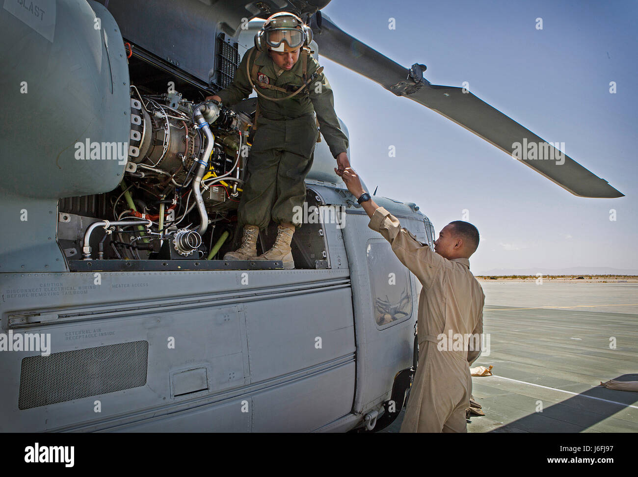Marines with Marine Light Attack Helicopter Squadron (HMLA) 469 conduct maintenance on a UH-1Y Venom during Integrated Stock Photo