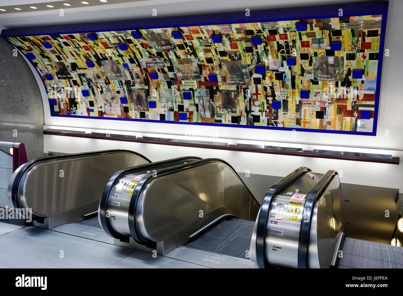 Atlanta Georgia Hartsfield-Jackson Atlanta International Airport escalator up down mural public art Saints Radcliffe - Stock Image