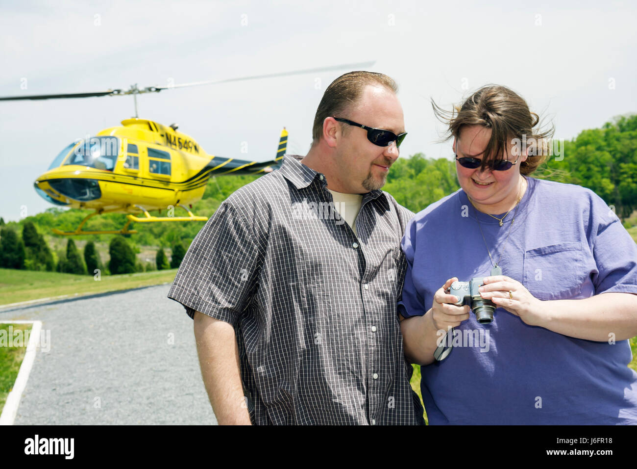 Tennessee Sevierville Scenic Helicopter Tours flight tour landing pad man woman couple camera - Stock Image
