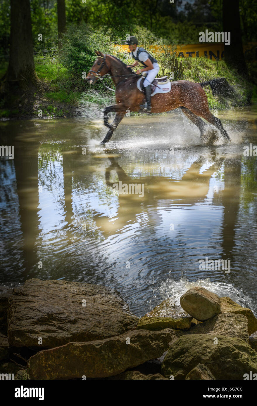 Rockingham Castle, Corby, UK. 21st May, 2017. Jack Pinkney and his horse LB Liberator splash pass through the water - Stock Image