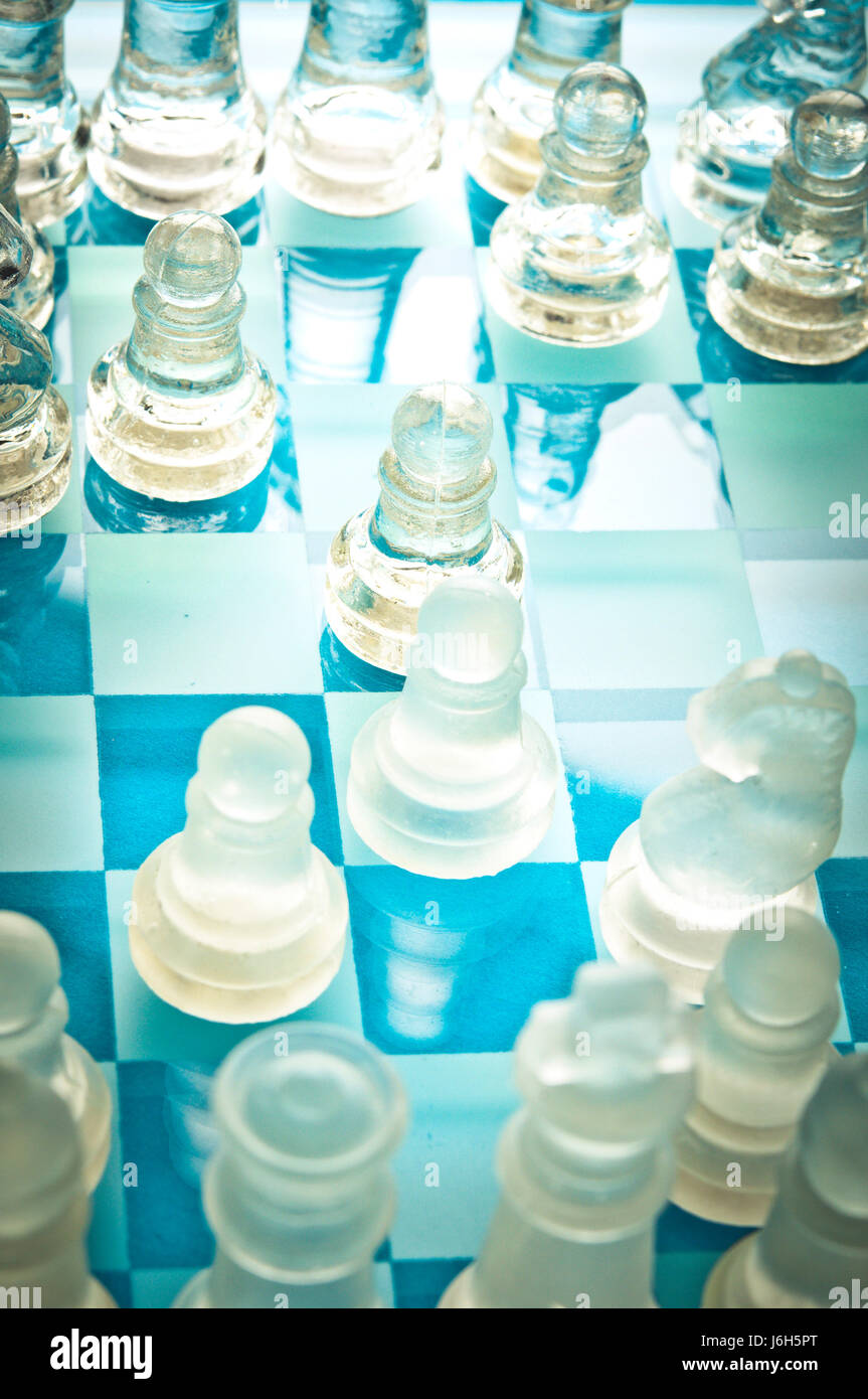 chess pieces and chessboard in glass, game in progress - Stock Image