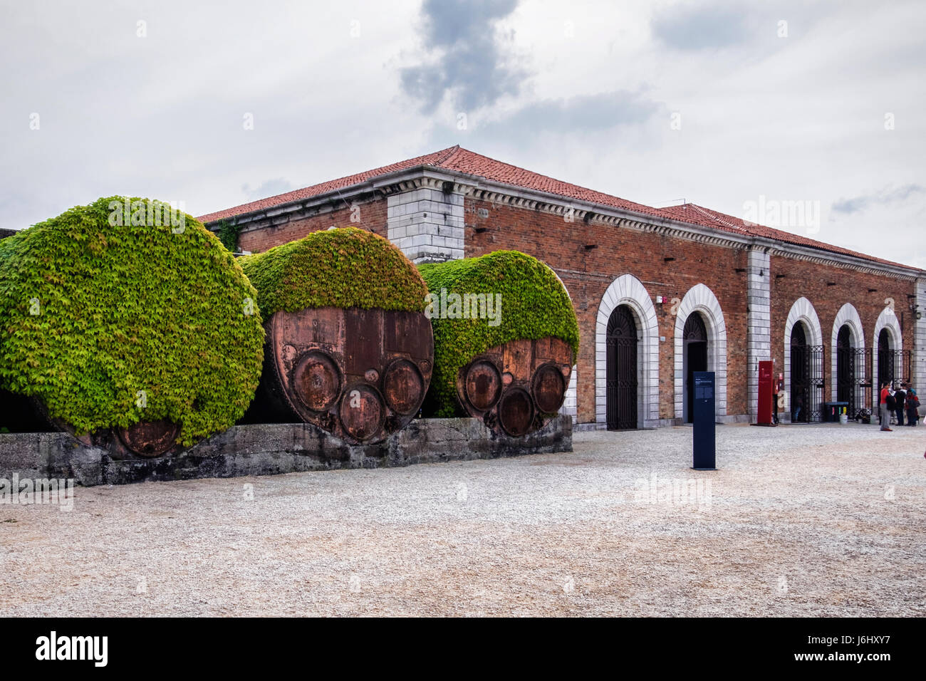 Venice, Castello, Arsenale harbour. Industrial rusty old iron barrel containers  covered in ivy next to historic - Stock Image
