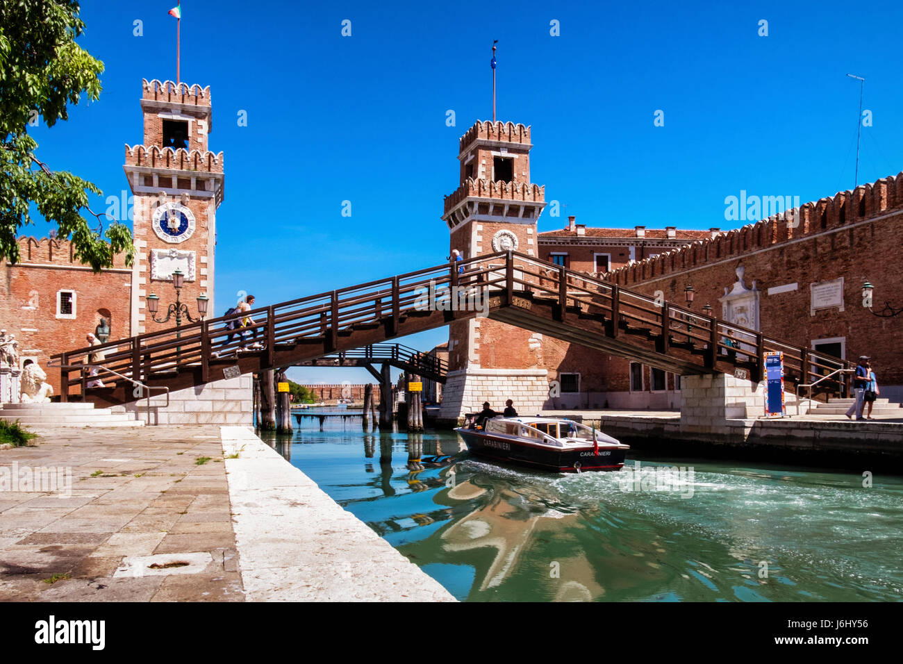 Arsenale,Venice, Italy - Entrance to the Naval Arsenal with Clock towers and and tourists crossing bridge over Rio Stock Photo