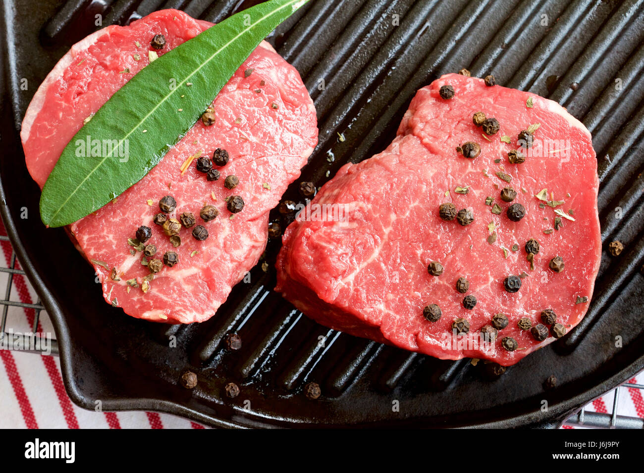 Raw beef eye fillet steak and peppercorns. - Stock Image