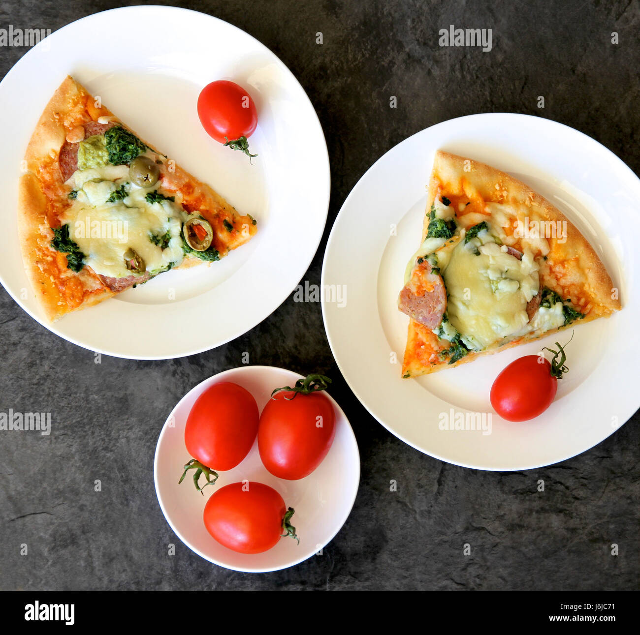 Pizza slice and red tomatoes on plates. - Stock Image