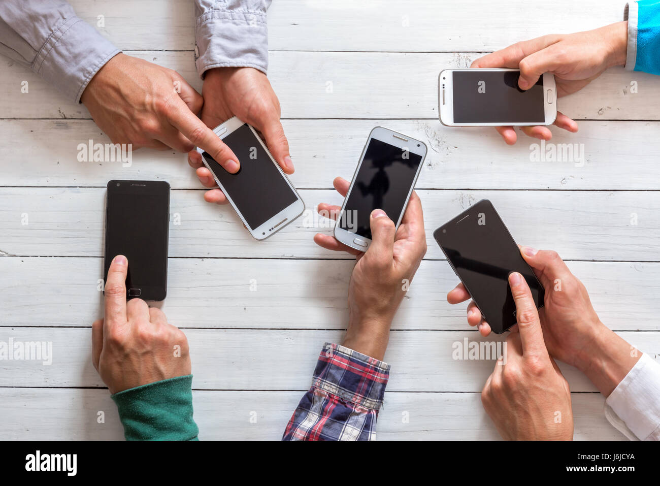 Mobile phones in friends hand closeup. Network addicted concept - Stock Image