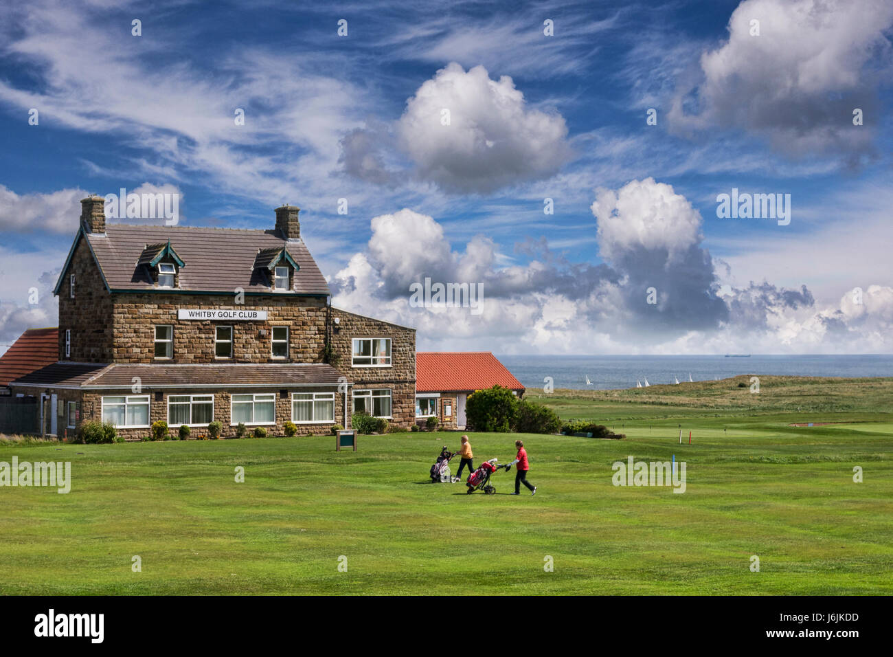 Two lady golfers walk in front of Whitby Golf Club with their golf trolleys, Whitby, North Yorkshire, England, UK, - Stock Image