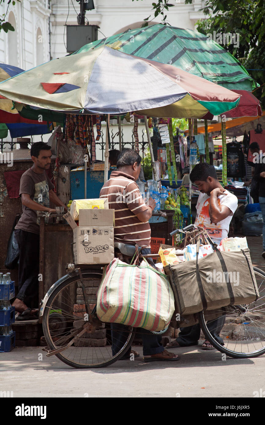 Man with bicycle speaking to a stall holder on Chowringhee Road Kolkata - Calcutta - West Bengal India - Stock Image