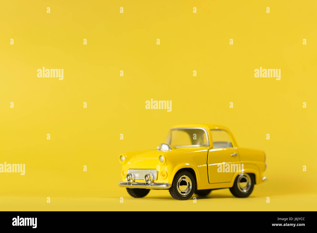 Yellow toy car on a yellow background. Stock Photo