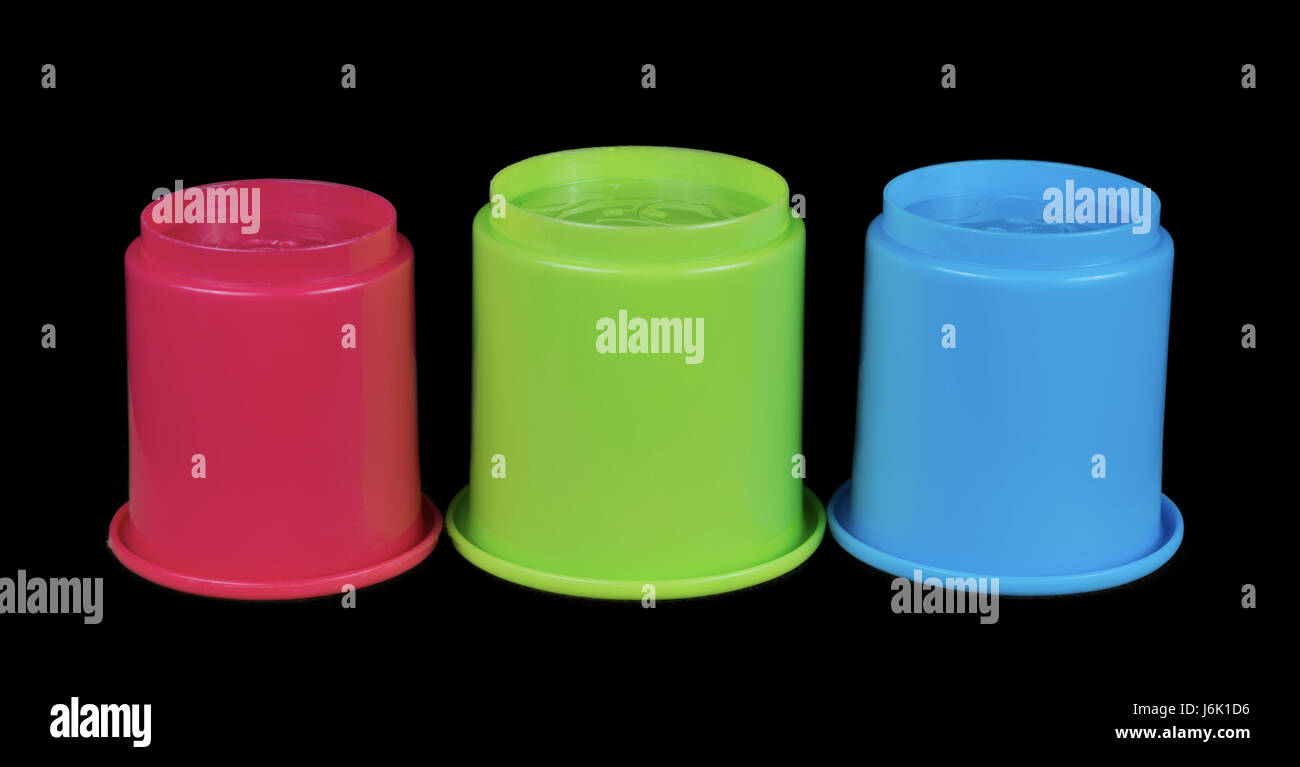 Children's red green and blue building cups that can be stacked but in this image are in a row and isolated - Stock Image